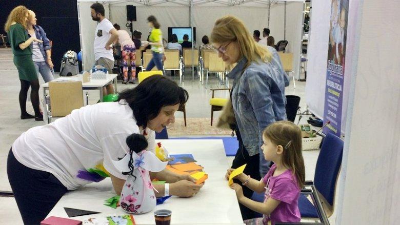 """Przedstawicielka Warsztatów Terapii Zajęciowej """"Tęcza"""" pokazywała, jak zrobić barwne motylki metodą origami (fot. SilesiaDzieci.pl)"""